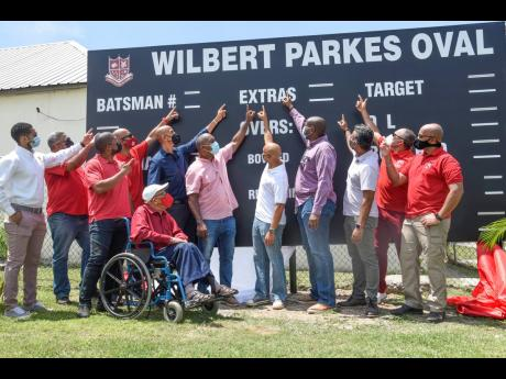 Former Campion College cricket coach Wilbert Parkes (fifth left) looks on as school alumni, including member of parliament for South East St Andrew Julian Robinson (seventh left), unveil the scoreboard bearing his name at the Wilbert Parkes Oval on the cam
