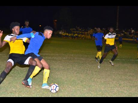 Tevoy Colespring (second left) of Meadforest FC holds off Barbican FC's Damian English during their KSAFA Super League first-round clash at Constant Spring Sports Complex on Saturday, February 2, 2019.