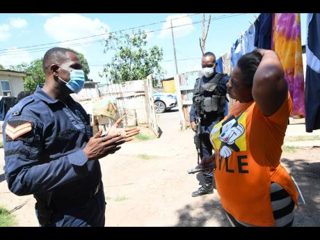 Policemen speak with Annmarie Lawman on Friday about the shooting death of her 16-year-old stepson Joel Lawman two days earlier in Old Harbour, St Catherine.