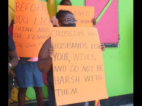 Protesters gather at the town square in Whithorn, Westmoreland, on Friday demonstrating  against violence against women.