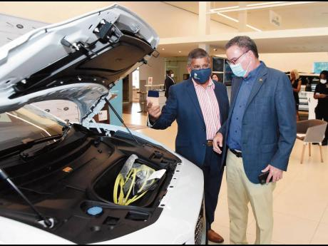 British High Commissioner to Jamaica, Asif Ahmad CMG shows Energy Minister Daryl Vaz that there's no engine under the bonnet of the all-electric 2021 Jaguar I-Pace at its official launch on Thursday, April 8 at Stewart's Automotive Jaguar Land Rover sh