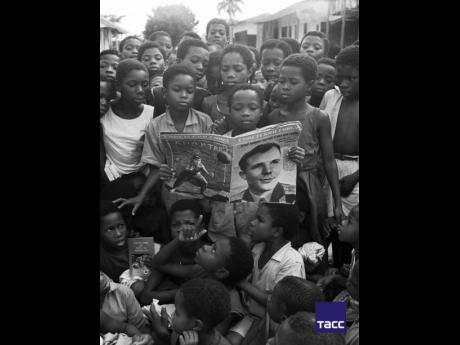 "School children in Ghana gather around to ""Soviet Union"" magazine with a portrait of Yuri Gagarin, the first astronaut, June 1961."