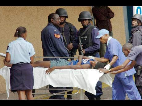 File  Porters take a young man who had sustained gunshot wounds to the shoulder to the Accident and Emergency Department at the Kingston Public Hospital in this May 2010 photo.