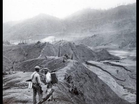 In this 1902 photo provided by York Museums Trust, men survey the devastation of the landscape following eruptions of La Soufrière, a volcano on the island of St Vincent.