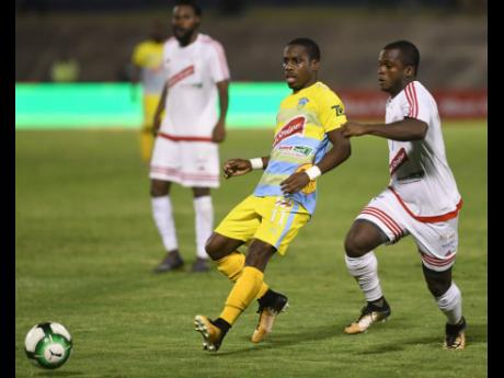 In this file photo from April 2018, then Waterhouse FC player Tremaine Stewart (left) is tracked by Portmore United's Kemar Phillpotts during their Jamaica Premier League final at the National Stadium.