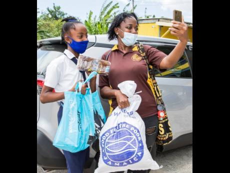 A mother and her daughter show off what they received in their care package on a video call to other family members. The care packages were delivered by New Fortress Energy Foundation and Food for the Poor to parents with students on the PATH programme in