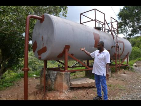 Devon Wilks, president of the Ginger Ridge Community Development Committee (CDC) in Browns Hall, St Catherine, points to the water tank that was acquired through the effort of that organisation.