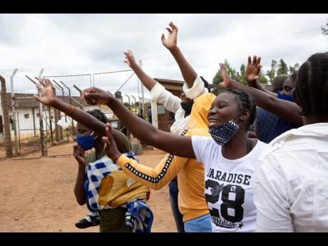 Female prsioners wave goodbye to their fellow inmates following their release from Chikurubi prison on the outskirts of Harare on Saturday.