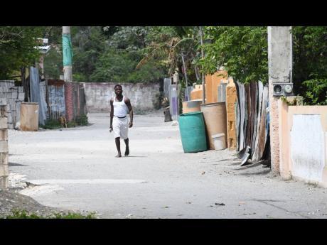 A youth walks along a dusty road in Grants Pen, St Thomas.