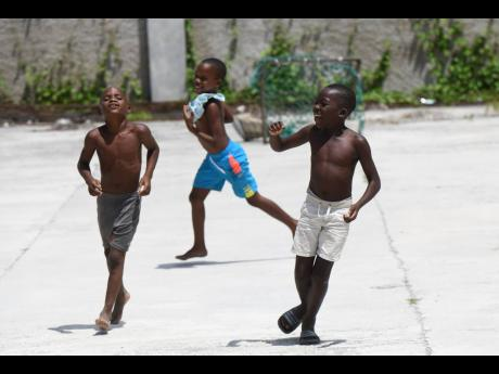 Youngsters playing on concrete in a yard in Grants Pen, St Thomas, on Saturday. There is no playing field in the community.