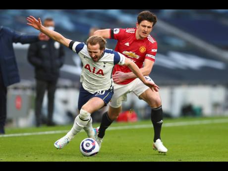 Tottenham's Harry Kane (left) is challenged by Manchester United's Harry Maguire during their English Premier League match at the Tottenham Hotspur Stadium in London, England on Sunday, April 11. UEFA President Aleksander Ceferin says players at the 12