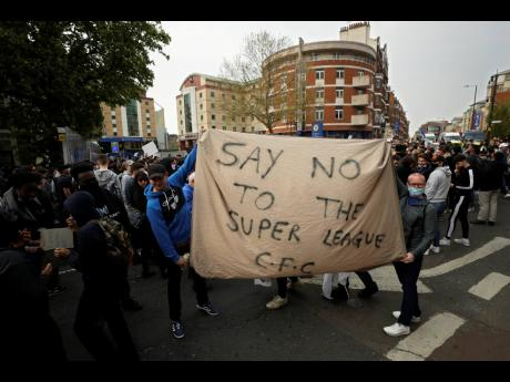 Chelsea fans protest outside Stamford Bridge stadium in London, against Chelsea's decision to be included amongst the clubs attempting to form a new European Super League, Tuesday, April 20, 2021. Reaction to the proposals from 12 clubs to rip up European