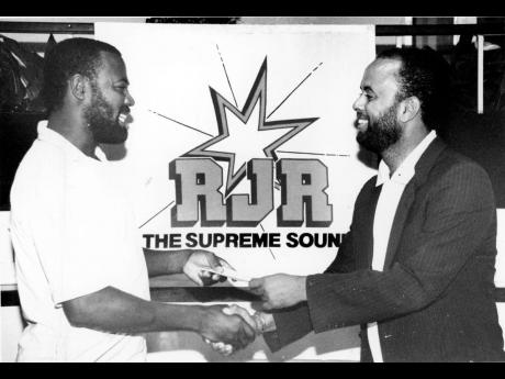 Roxcosmo Thomas (left), emerged as the winner in the 'Sharp Talk Election Quiz', which was conducted on Radio Jamaica (RJR). Here, Roxcosmo accepts his cheque for $5,000 from Michael Sharpe, host of 'Sharp Talk', for correctly predicting which par