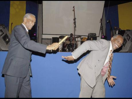 In a symbolic gesture, Dr Rae Davis (left), former UTech president, passes a gold baton to his successor, Professor Errol Morrison. The occasion was a farewell function for Davis held at UTech on March 21, 2007.