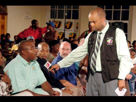 In this July 2006 file photo, then president of the St James Taxi Association, Dion Chance, answers Television Jamaica host Michael Sharpe during a town-hall discussion. Sharpe, 65, died on Tuesday.