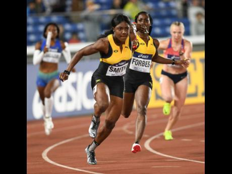 Jonielle Smith (left) receives the baton from Shashalee Forbes in the women's 4x100 metre relay heats at the IAAF World Relays in Yokohama, Japan in 2019.