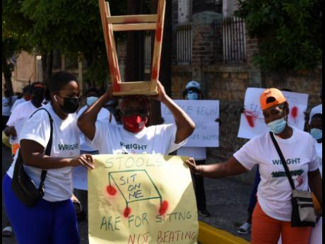Scores of protesters demonstrate against domestic violence near the Parliament building on Duke Street, Kingston, on Tuesday.