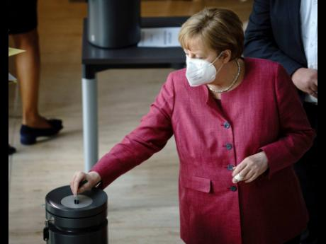 Chancellor Angela Merkel puts her voting card in the ballot box during the Bundestag session in Berlin, Germany, on Wednesday, April 21, during the vote on the expanded Infection Protection Act to contain the coronavirus pandemic.