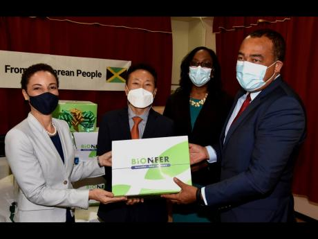 Minister of Health and Wellness Dr Christopher Tufton (right) and Minister of Foreign Affairs and Foreign Trade, Senator Kamina Johnson Smith (left), display some of the COVID-19 testing supplies donated by the Embassy of the Republic of Korea to support t