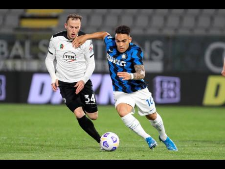 Spezia's Ardian Ismajli (left) and Inter Milan's  Lautaro Martinez compete for the ball during their Italian Serie A match at the Alberto Picco stadium in La Spezia yesterday. The match ended 1-1.