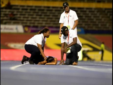 Bethany Bridge of Edwin Allen is attended to by medical personnel after suffering an injury,while competing in the 200m Class Two event at the ISSA/GraceKennedy Boys and Girls' Athletics Championships at the National Stadium on Thursday, March 28, 2019.