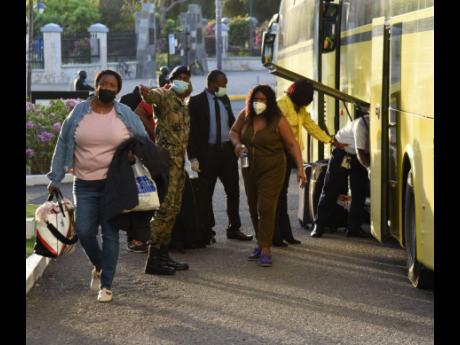 A soldier and other health officials give directives as 27 persons who arrived from the United Kingdom on a repatriation flight yesterday disembarked buses to begin their quarantine period at The Jamaica Pegasus hotel in New Kingston.