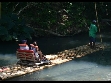 In this April 2019 Gleaner photo, a raft captain guides two clients on the three-mile journey down the Martha Brae River in Trelawny.