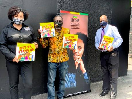 From left: Manager of the Bob Marley Foundation, Alicia Williams; Owen 'Blakka' Ellis, president of the Optimist Club of Trench Town; and Dr Henley Morgan, founder and chairman of Agency for Inner-City Renewal show off some of the books to be used to t