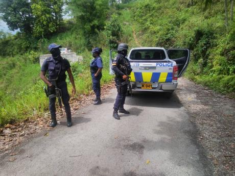 Police officers attached to the St Elizabeth Police Division combing a section of Bronte Common community for illegal weapons, at the location where three alleged gunmen were shot and killed Thursday evening after they challenged the police in a shoot-out.