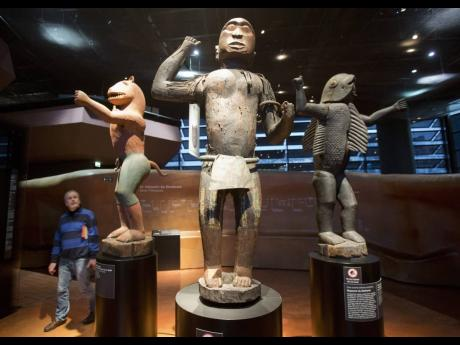 A visitor looks at wooden royal statues of the Dahomey kingdom, dated 19th century, today's Benin,at Quai Branly museum in Paris, France, in November 2018. From Senegal to Ethiopia, artists, governments and museums are eagerly awaiting a report commissi