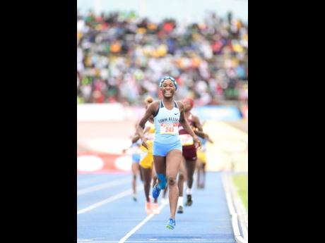 Rushana Dwyer of Edwin Allen is all smiles as she prepares to cross the finish line on her way to winning the Class Two girls 800m finals at the ISSA/GraceKennedy Boys and Girls' Athletics Championships at the National Stadium on Saturday, March 30, 201