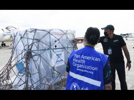 Dr Bernadette Theodore-Gandi, representative of the Pan American Health Organization, and Health Minister Dr Christopher Tufton observe a shipment of 55,200 doses of Oxford-AstraZeneca COVID-19 vaccine that arrived at the Norman Manley International Airpor