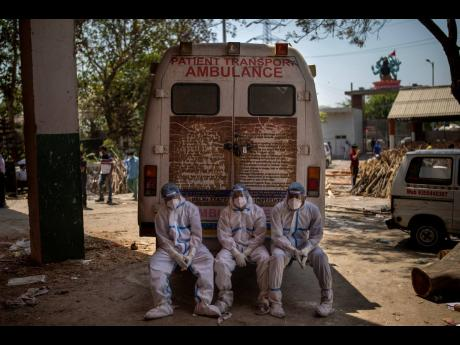 Exhausted workers, who bring dead bodies for cremation, sit on the rear step of an ambulance inside a crematorium in New Delhi, India, on Saturday, April 24. India is suffering a bigger, more infectious second wave of the coronavirus, with more than 300,00