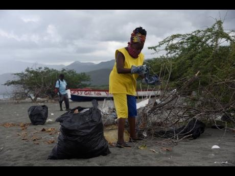 Constance Worrell, president of the South Albion Farmers' Group, detaches a piece of clothing from a cluster of branches during a beach clean-up in Cow Bay, St Thomas.