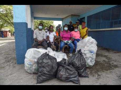 Some of the team members took a 10-minute break during a beach clean-up in Cow Bay, St Thomas.