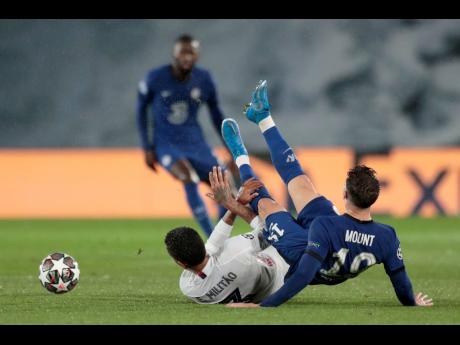 Real Madrid's Eder Militao (left) and Chelsea's Mason Mount fall down during the Champions League semi-final first leg match between Real Madrid and Chelsea at the Alfredo di Stefano stadium in Madrid, Spain, yesterday. The match ended 1-1.