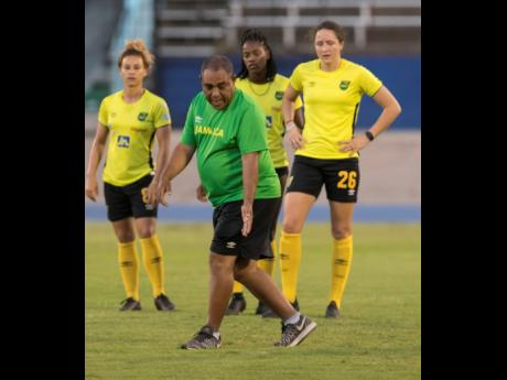 Former Reggae Girlz head coach Hue Menzies (foreground) gives instructions during a training session at the National Stadium on Monday, May 13, 2019, ahead of an international friendly against Panama.