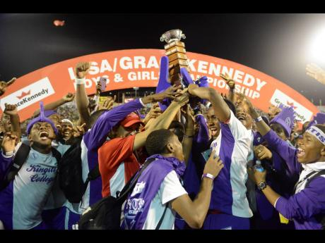 Don Wehby, Group CEO at GraceKennedy, is smothered by jubilant Kingston College athletes as he presents the Mortimer Geddes Trophy to the team after their success at the 2019 ISSA/GraceKennedy Boys and Girls' Athletics Championships at the National Stadi