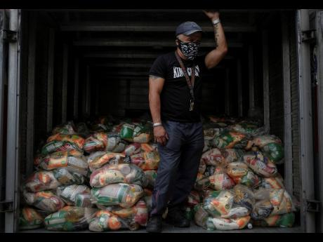 On April 10, a man waits to unload bags of basic food staples provided to residents through the CLAP government food assistance programme in the Santa Rosalia neighbourhood of Caracas, Venezuela.