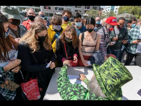 A man wearing a cannabis costume hands out marijuana cigarettes in New York during a 'Joints for Jabs' event, where adults who showed their COVID-19 vaccination cards received a free joint.