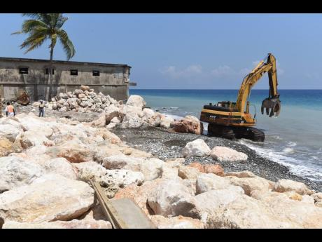 A tractor ventures into the sea in Buff Bay, Portland during construction of a seawall.