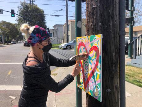 Artist Deirdre Freeman hangs her artwork on a telephone pole in Alameda, California.