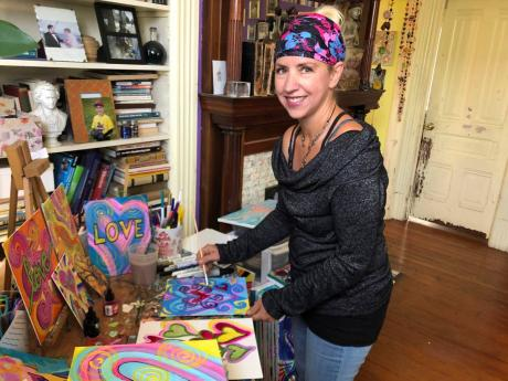 """Artist Deirdre Freeman poses in her studio in Alameda, California. Freeman, who has hung over 120 pieces of artwork on telephone poles to spread joy to others, says, """"It's starting a love and kindness movement, which is what we need."""""""