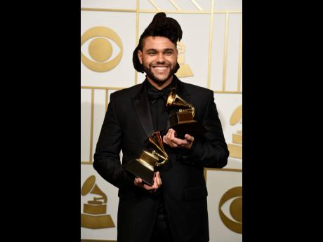 The Weeknd poses in the press room with the awards for Best R&B Performance for 'Earned It (Fifty Shades of Grey)' and Best Urban Contemporary Album for 'Beauty Behind The Madness' at the 58th annual Grammy Awards in Los Angeles in 2016. The Grammy Awards