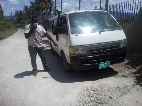 An irate Kamal Byrd points to his vehicle which he claims was damaged as a result of the poor conditions of the roads.