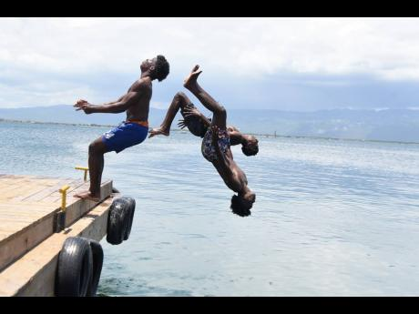 Thadius Brown (right), 19, Ronaldinho Brown (centre), 19, and 18-year-old Prince Bryan dive off the Port Royal Pier on Saturday.