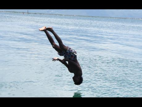 Prince Bryan, 18, leaps off the Port Royal Pier. Bryan, one of several teenagers who are members of JAPROS swimming club, edits videos of their exploits and posts them to a YouTube channel that is generating a buzz.