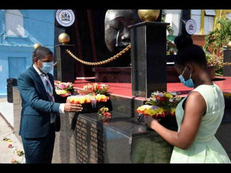 Delroy Williams, mayor of Kingston, and Reajean Bennett, acting youth mayor, pay respect by laying wreaths on the Secret Gardens Monument, in memory of children who have died tragically, at the intersection of Tower and Church streets in the capital on Sun