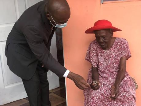 105-year-old Roberta Gayle receives the keys to her new house from Pastor Glen Samuels, president of the West Jamaica Conference of Seventh-day Adventists. The presentation took place on Sunday, March 21 in Lacovia, St Elizabeth. The new house replaced a d