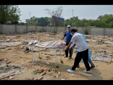 The body of a COVID-19 victim is wheeled in a ground that has been converted into a crematorium in New Delhi, India, on Saturday